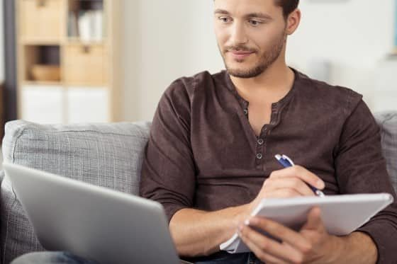 Young man taking notes while reading