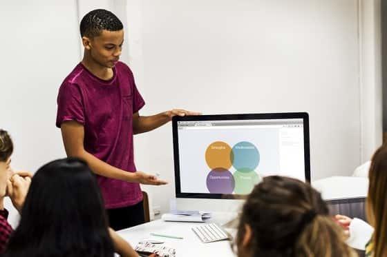 Man pointing at computer screen giving a presentation