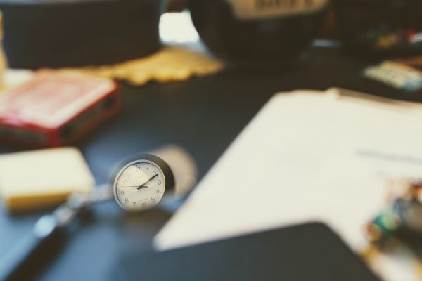 a watch sits on a desk surrounded by papers