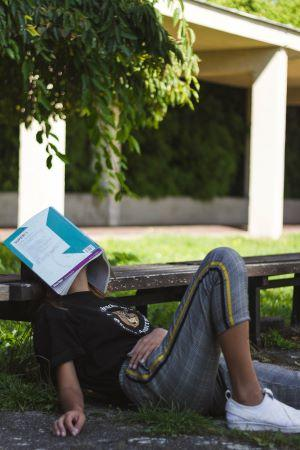 a student lays on the grass with a book open over their face