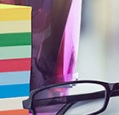 glasses and a stack of Post-It notes on a desk