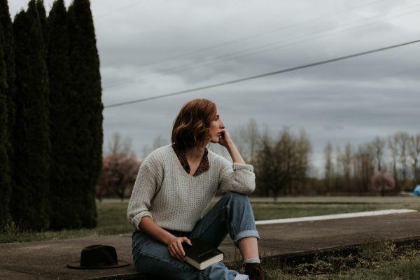 A woman sits on the pavement looking worried