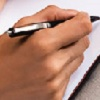 a hand holds a pen above a blank notebook