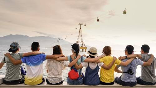 Group of young students with arms around each other looking out over the sea