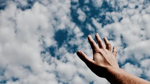 Hand reaching out to a cloudy sky