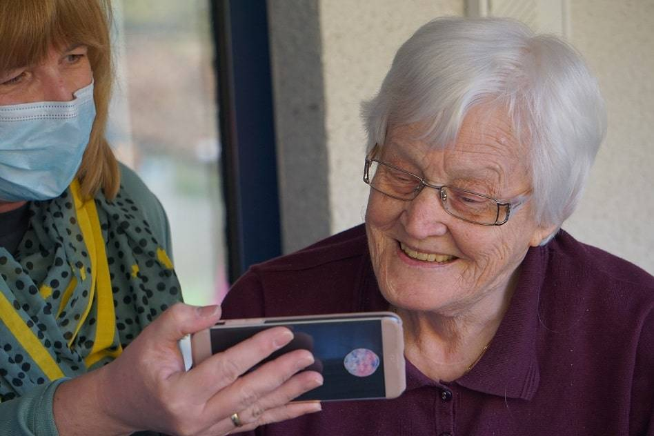 Older person, caregiver, mask, building relationship, relational care, looking at phone